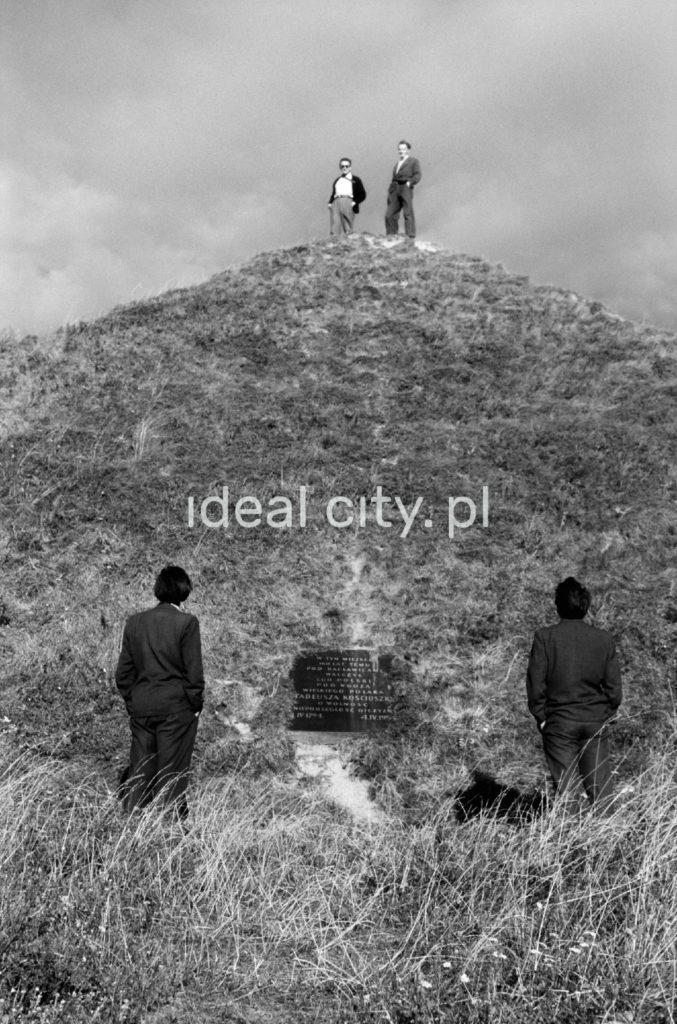 Dwaj mężczyźni stoją ze szczycie pagórka, gdy dwaj kolejni przyglądają im się. Widoczna tablica pamiątkowa.
