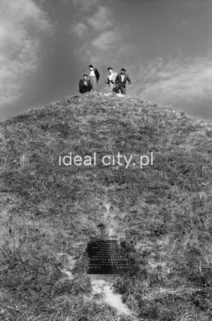Czterej mężczyźni stoją na szczycie pagórka. Widoczna tablica pamiątkowa.