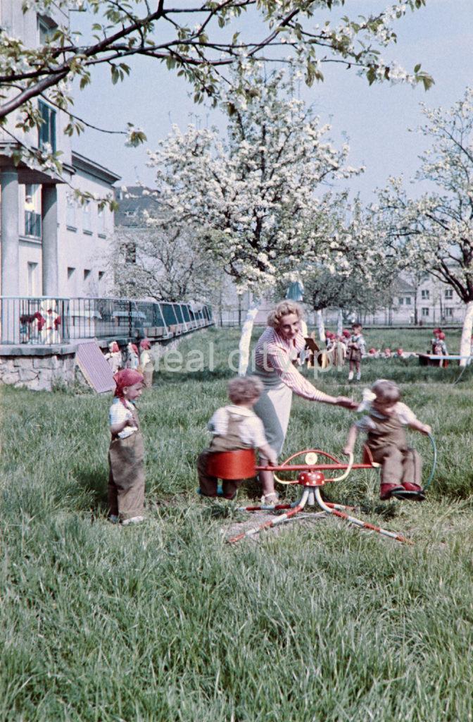 Przedszkolanka z dziećmi na trawniku przed modernistycznym pawilonem.