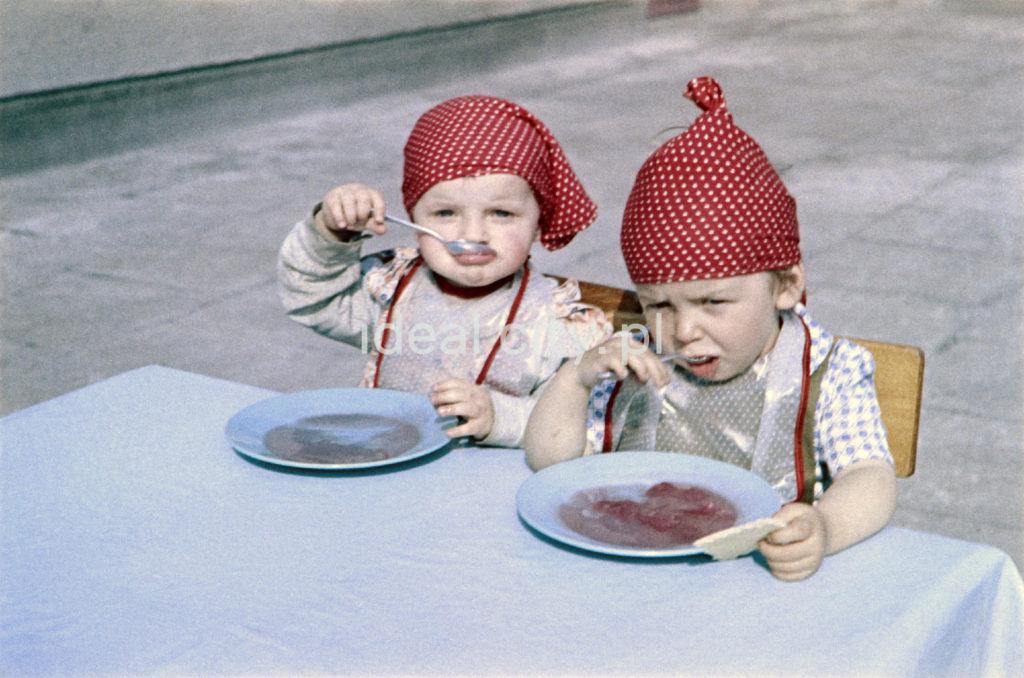 Dzieci w czerwonych hutskach na głowach jedzą zupę z talerzy.