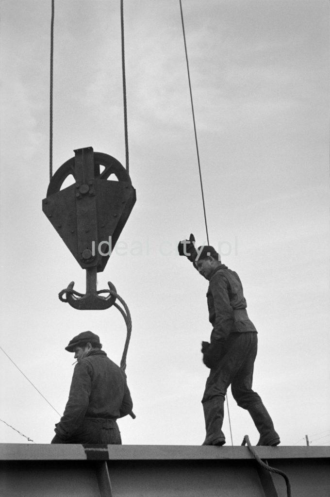 Dwóch robotników montuje linę na zwisającym z góry potężnym haku podnośnika.