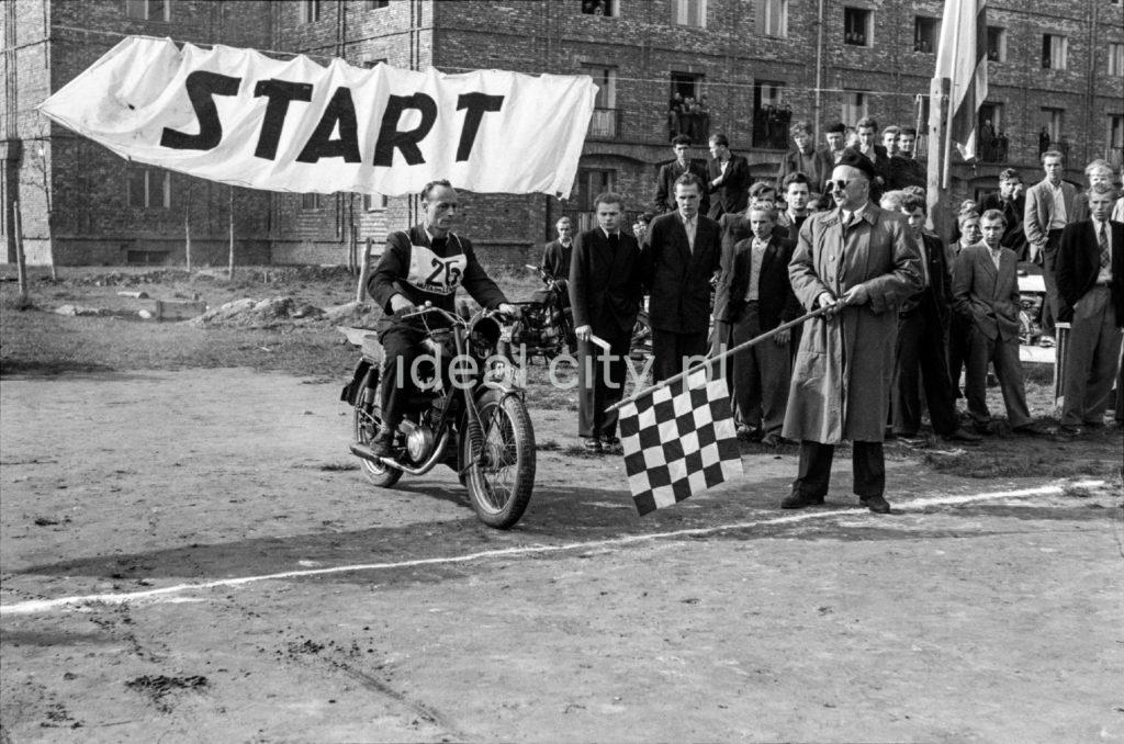 Motocyklista w garniturze na linii startu wyścigu ulokowanej na placu przed blokiem.