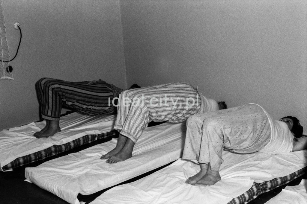 Trzy kobiety w piżamach wypychają do góry brzuchy w trakcie ćwiczeń na swoich szpitalnych łóżkach.