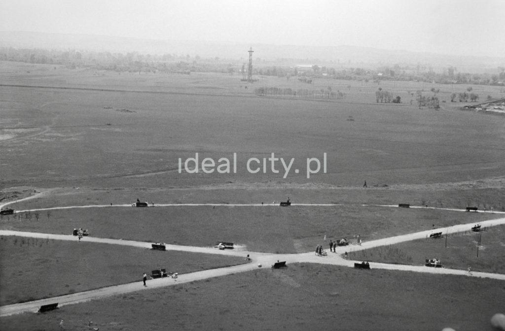 Ujęcie z góry na łąkę poprzecinaną chodnikami, przy których ulokowane ławki zapełnili przechodnie. W perspektywie łąka i wieża spadochronowa.