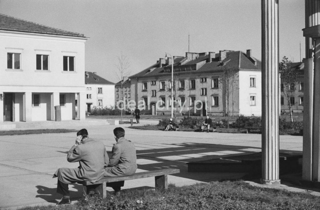 Dwóch mężczyzn w prochowcach siedzi na ławce na niewielkim miejskim placu, dookoła bloki.