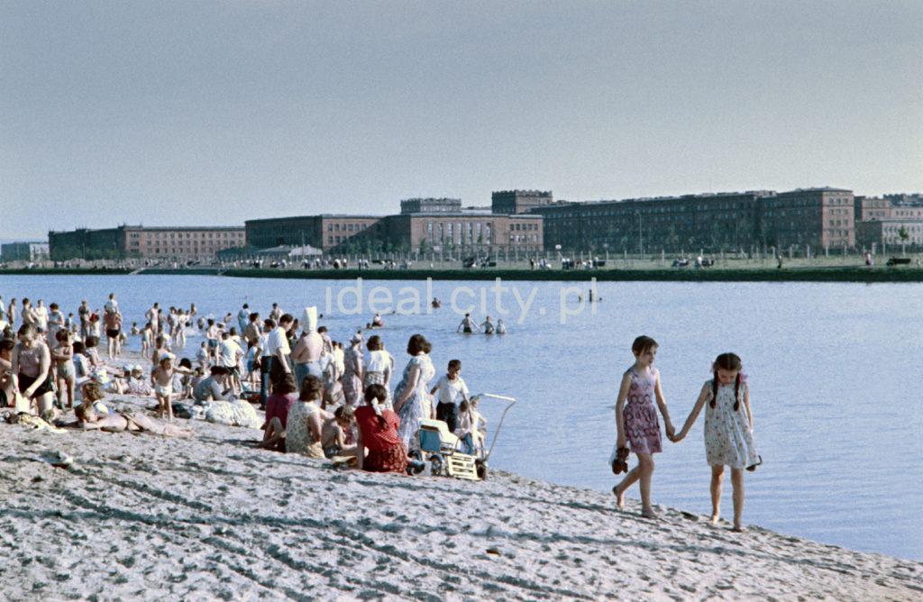 Na piaszczystej plaży wypoczywają ludzie, na pierwszym planie dwie dziewczynki, w tle, na drugim brzegu intensywna zabudowa z cegły.
