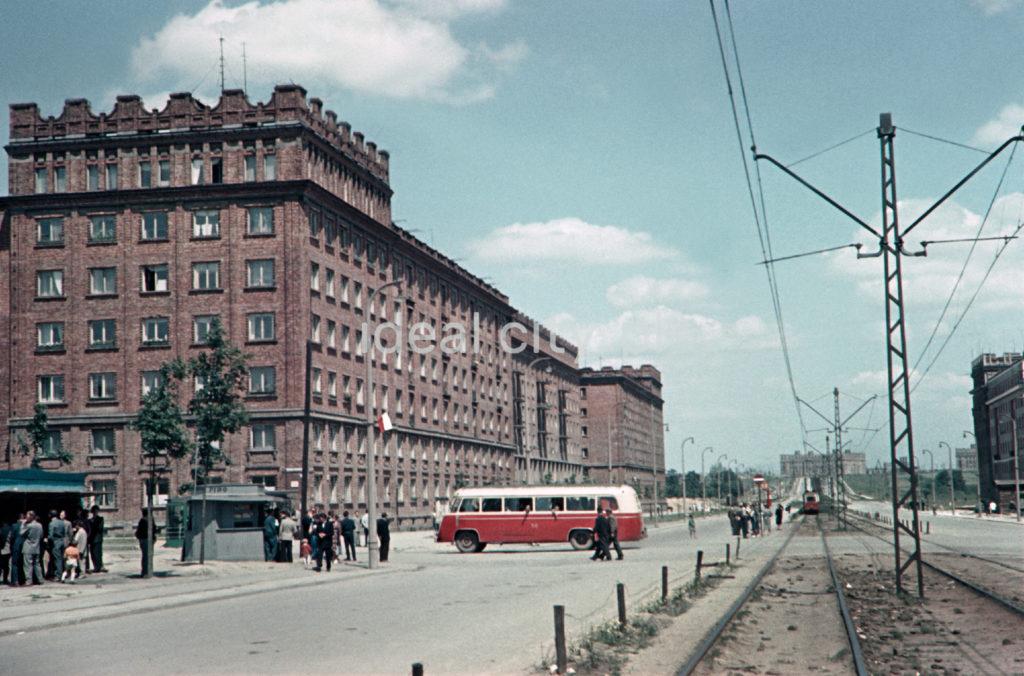 Ujęcie na linię tramwajową, którą przecina biało-czerwony autobus, po lewej monumentalny blok z cegły.