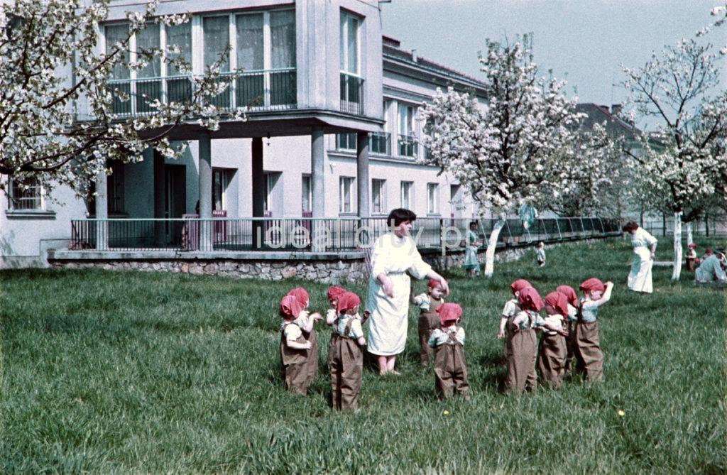 Przedszkolanka zwołuje do siebie dzieci, których głowy przykryte są przed słońcem czerwonymi hustami, w tle modernistyczny pawilon przedszkola.