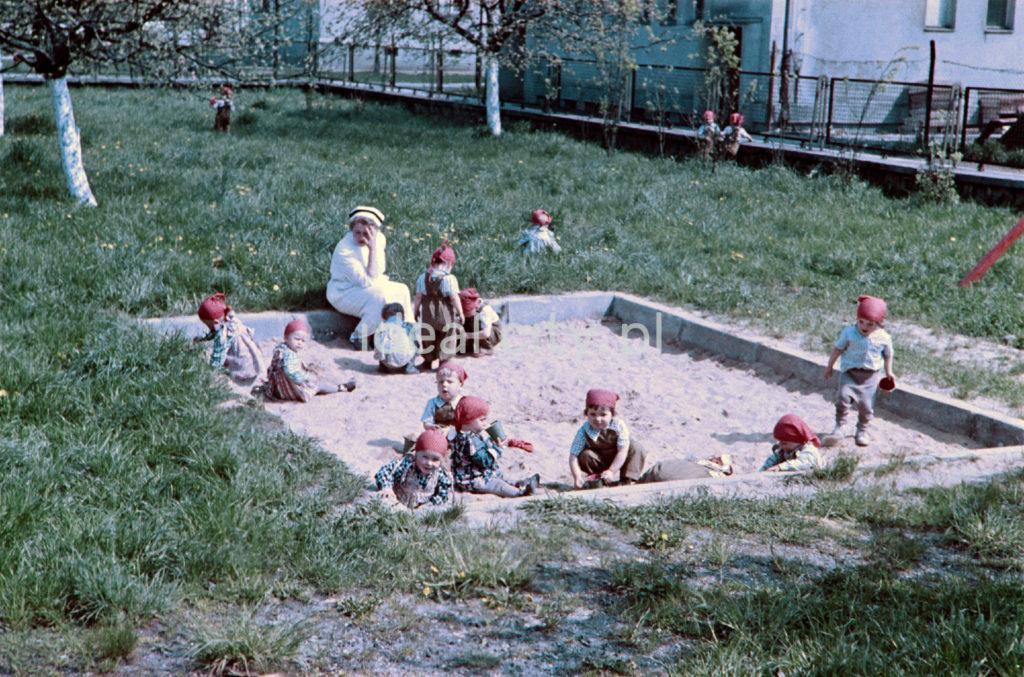 Dzieci w czerwonych hustach na głowach bawią się w piaskownicy.